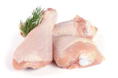 Three raw chicken drumsticks with a sprig of dill isolated on white background.  Stock Images