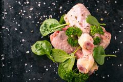 Three raw chicken legs on black tray with green herbs Stock Photos