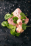 Three raw chicken legs on dark tray with herbs Stock Images