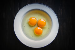 Three raw eggs in white metal plate. On a black background, dark wooden table Royalty Free Stock Image