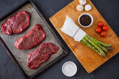 Three raw filet steaks with green asparagus, mushrooms Royalty Free Stock Photo