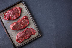 Three raw fillet steaks on an old baking tray Stock Image