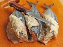 Three raw mackerels. On the chopping board Stock Photos