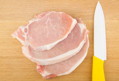 Three raw pork chops and knife Stock Image