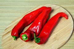 Three raw red pointed peppers. Stock Photos