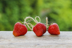 Three raw ripe strawberries on wooden table Royalty Free Stock Photo