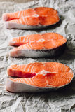 Three Raw Salmon Steaks on Parchment Paper. Vertical Royalty Free Stock Image
