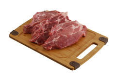 Three raw steaks on bamboo cutting board Royalty Free Stock Image