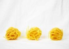 Three raw tagliatelle pasta Stock Photo