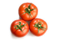 Three realistic looking tomatoes lying in a triangle isolated in white background Royalty Free Stock Image