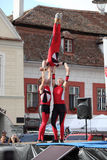 Three red acrobats on a trampoline Stock Photos