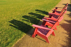 Three red adirondack chairs on a path Stock Photos