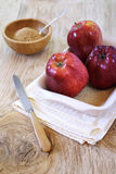 Three red apple in baking dish and brown sugar Stock Photos