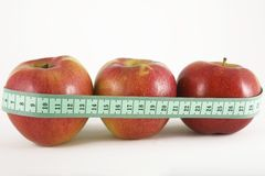 Three red apple and green measurement tape Stock Photos