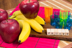 Three red apples, colored glasses and three bananas on wooden surface with the writing fruits Royalty Free Stock Image