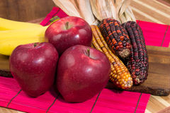 Three red apples, corn and bananas on wooden surface Stock Photos