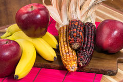 Three red apples, corn and three bananas on wooden surface Royalty Free Stock Photo