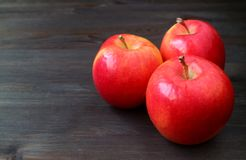 Three red apples on dark colored wooden table with free space for text and design royalty free stock photography