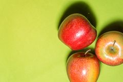 Three red apples on green tablecloth royalty free stock photo