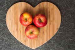 Three red apples on Heart Shaped Chopping Board. Three red and yellow apples on Heart Shaped Chopping Board Royalty Free Stock Photography