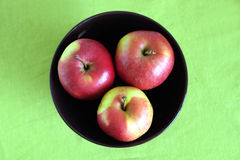 Three red apples inside purple bowl clos-up. Three red apple inside purple bowl on green tablecloth top view closeup Royalty Free Stock Image