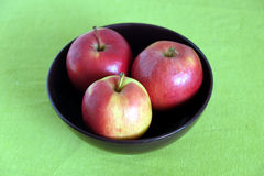 Three red apples inside purple bowl close-up. Three red apple inside purple bowl on green tablecloth top view closeup Stock Images