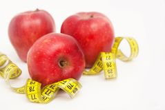 Three Red Apples Isolated on White Background. Fat Burning and Weight loss process. Tape Measure. Copy space. Royalty Free Stock Photo