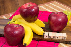 Three red apples and three bananas on wooden surface with the writing fruits Royalty Free Stock Images