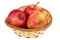 Three red apples in wicker basket isolated on white Stock Image