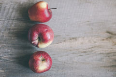 Three red apples on wood board Stock Photography