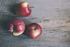 Three red apples on wood board Stock Image