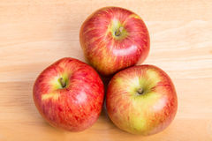 Three Red Apples on Wood Table Stock Images
