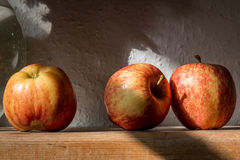 Three red apples on a wooden shelf - still life Stock Photography