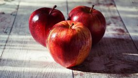 Three Red Apples on Wooden Surface royalty free stock image