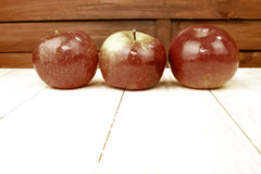 Three red apples on wooden table Royalty Free Stock Photos