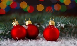 Three Red balls over blurred lights background with fir branch. Christmas and New Year Decoration. Royalty Free Stock Image
