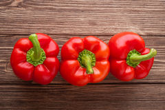 Three red bell peppers on a wooden background. Top view. Three ripe red bell peppers Stock Photos