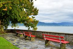 Three red benches facing beautiful Bodensee lake on rainy autumn day in Lindau, Germany. Three red benches facing beautiful Bodensee lake on rainy autumn day in Stock Images