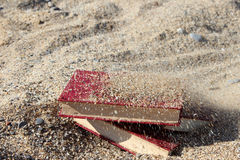 Three red books on the sand, covered with sand, concept of transience of time, blurred background. Royalty Free Stock Photo