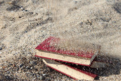 Three red books on the sand, covered with sand, concept of transience of time, blurred background. Stock Images