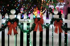 Three red bows with a garland. Connecting them on the white wooden fence royalty free stock photo