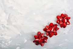 Three red bows on rude grey background Royalty Free Stock Photo