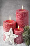 Three red candles on gray background, Christmas decoration. Adve. Nt  mood Royalty Free Stock Image