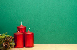 Three red candles on green background Stock Images