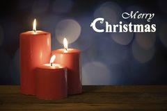 Three red candles with Merry Christmas text royalty free stock photo