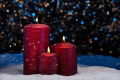 Three Red Candles in snow Stock Images