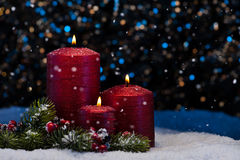 Three Red Candles in snow Royalty Free Stock Photos