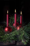 Three Red Candles 2. Three red candles in sprays of pine boughs with red Christmas ornaments and dark background Stock Photo