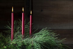 Three Red Candles. In sprays of pine boughs with dark wooden background Stock Photo