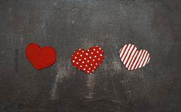 Three red cardboard hearts on grunge. Red, polka dot and striped cardboard heart-shaped symbols on grunge shabby background n stock images